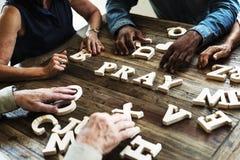 Groupe de personnes la disposition un mot sur la table en bois photo stock