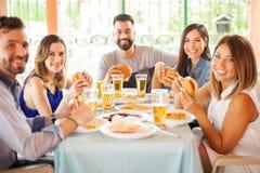 Groupe de personnes mangeant des hamburgers Images stock