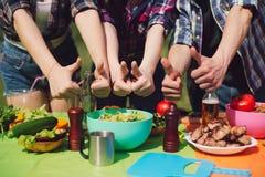 Groupe de personnes montrant des pouces jusqu'à la table de la nourriture Image stock
