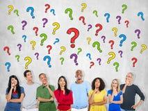 Groupe de personnes multi-ethnique pensant et points d'interrogation Image libre de droits