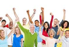 Groupe de personnes multi-ethnique soulevant leurs bras Image stock