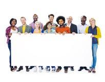 Groupe de personnes multi-ethniques tenant la plaquette vide Image libre de droits