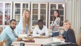 Groupe de personnes multiraciales étudiant avec des livres à la bibliothèque universitaire clips vidéos