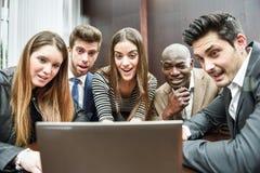 Groupe de personnes occupées multi-ethniques regardant un ordinateur portable image libre de droits