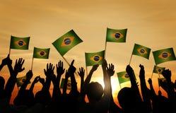 Groupe de personnes ondulant les drapeaux brésiliens dans le Lit arrière Images stock