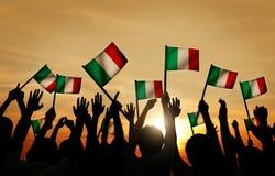 Groupe de personnes ondulant les drapeaux italiens dans le Lit arrière Images stock