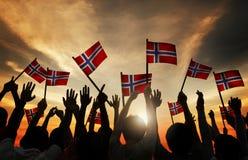 Groupe de personnes ondulant les drapeaux norvégiens dans le Lit arrière Photos libres de droits