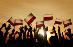 Groupe de personnes ondulant les drapeaux polonais dans le Lit arrière Photo libre de droits