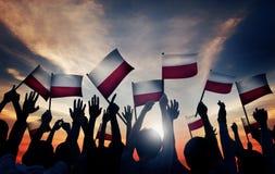 Groupe de personnes ondulant les drapeaux polonais dans le Lit arrière Photographie stock libre de droits