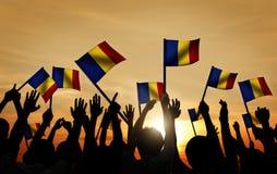 Groupe de personnes ondulant les drapeaux roumains dans le Lit arrière Photographie stock libre de droits
