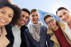 Groupe de personnes ou d'amis heureux sur la rue de ville photo stock