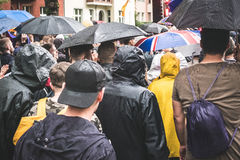 Groupe de personnes par derrière la marche sous la pluie avec des parapluies Photographie stock