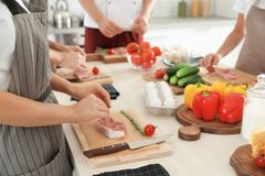 Groupe de personnes préparant la viande aux cours de cuisine photographie stock