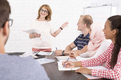 Groupe de personnes s'asseyant au bureau et regardant le haut-parleur Photos stock
