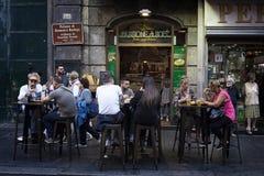 Groupe de personnes s'asseyant aux tables de rue tout en mangeant le foo de rue Photos stock