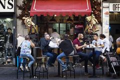 Groupe de personnes s'asseyant aux tables de rue tout en mangeant le foo de rue Photo stock