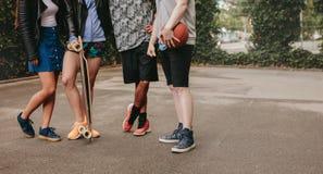 Groupe de personnes se tenant avec le basket-ball et la planche à roulettes Photographie stock libre de droits