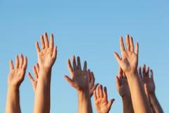 Groupe de personnes soulevant leurs mains dans le ciel Photos stock