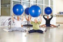 Groupe de personnes supérieures avec des boules de gymnase au centre de fitness Image stock