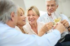 Groupe de personnes supérieures faisant le pain grillé avec le champagne Image libre de droits