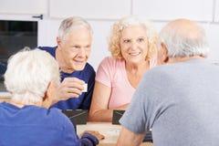 Groupe de personnes supérieures jouant le jeu de rummikub Photos stock