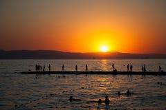 groupe de personnes sur la plage au coucher du soleil, silhouette des amis ayant l'amusement ensemble Photos libres de droits