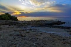 Groupe de personnes sur le bord observant le beau coucher du soleil coloré à la mer avec les nuages dramatiques et briller du sol images stock