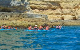 Groupe de personnes sur le canoë-kayak dans l'océan avec des montagnes Kayaks photos stock