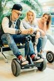 Groupe de personnes sur le hoverboard électrique de scooter se reposant au banc et à l'aide du téléphone photos libres de droits