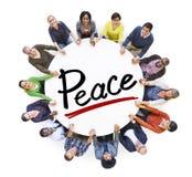 Groupe de personnes tenant des mains autour de la paix de lettre Photos libres de droits