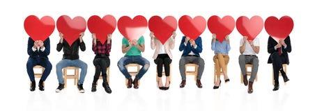 Groupe de personnes tenant de grands coeurs rouges au-dessus de leurs visages photo libre de droits