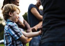 Groupe de personnes tenant la main ensemble en parc Image stock
