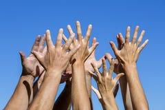 Groupe de personnes tirant des mains dans le ciel au soleil Beaucoup de mains sur le fond de ciel bleu Photos libres de droits