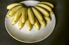 Groupe de petites bananes mûres non épluchées sur le plat blanc Photo stock