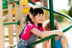 Groupe de petites filles heureuses sur le terrain de jeu d'enfants Photographie stock