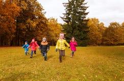 Groupe de petits enfants heureux courant dehors Photos stock