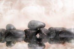 Groupe de pierres noires dans l'eau chaude avec le fond de vapeur Photo libre de droits