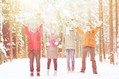 Groupe de playin heureux d'amis avec la neige dans la forêt Photos stock