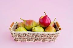Groupe de poires de viol dans le panier sur pâle - fond rose image stock