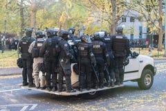 Groupe de police dans le tenue anti-émeute montant des côtés de la voiture photographie stock libre de droits