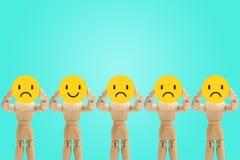Groupe de position en bois et de tenir de figure des émotions de visage dans la tristesse et le bonheur photographie stock libre de droits