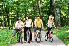 Groupe de quatre adultes sur des bicyclettes dans la campagne Images libres de droits