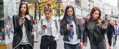 Groupe de quatre amie avec des smartphones sur la rue Photo libre de droits