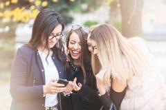Groupe de quatre amie regardant le téléphone sur le selfie ils W Photos libres de droits