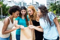 Groupe de quatre amies après des achats noirs de vendredi dans le CIT Photographie stock