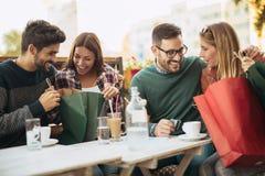 Groupe de quatre amis ayant l'amusement un café ensemble Photographie stock libre de droits