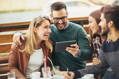 Groupe de quatre amis ayant l'amusement un café ensemble Images stock