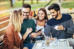 Groupe de quatre amis ayant l'amusement un café ensemble Images libres de droits