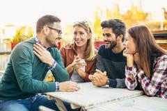 Groupe de quatre amis ayant l'amusement un café ensemble Photographie stock