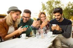 Groupe de quatre amis ayant l'amusement un café ensemble Image libre de droits